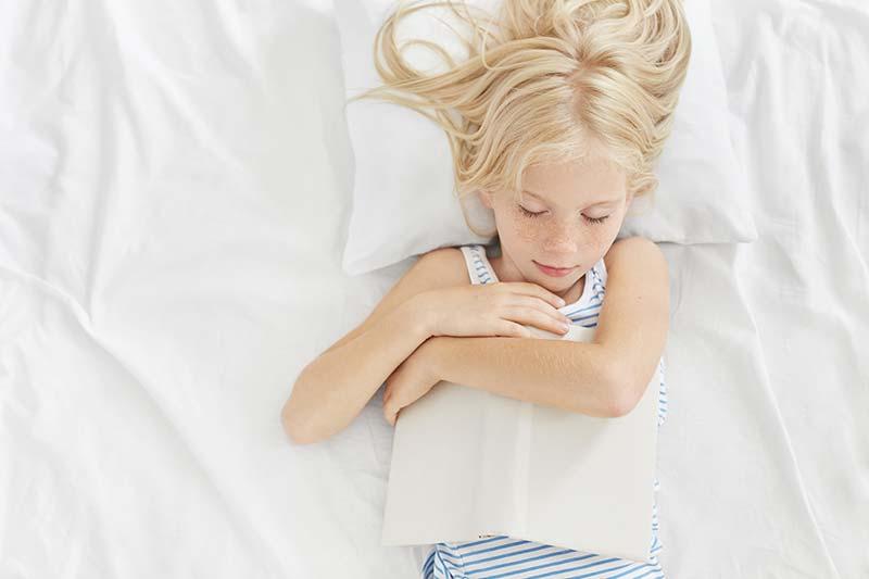 Kind in Kinderbettwäsche